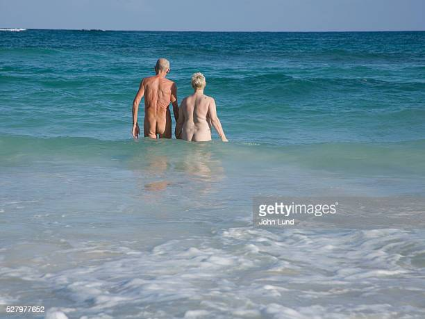 senior couple wading nude in ocean - old nudists stock pictures, royalty-free photos & images