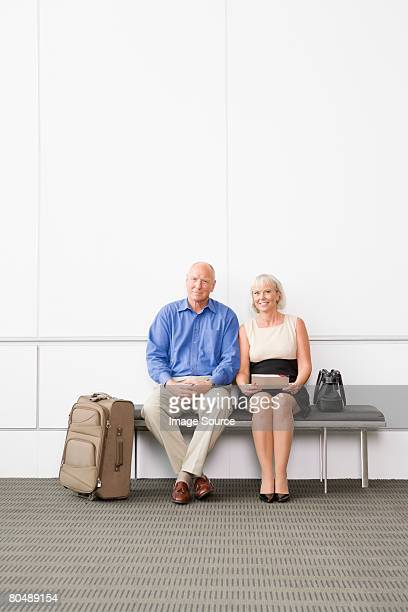A senior couple waiting on a bench