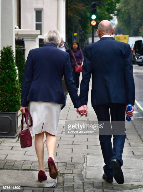 A senior couple walk handinhand along a sidewalk in the Belgravia district of London England