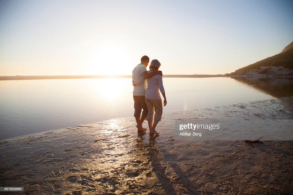 Senior couple walking along a beach : Stock Photo