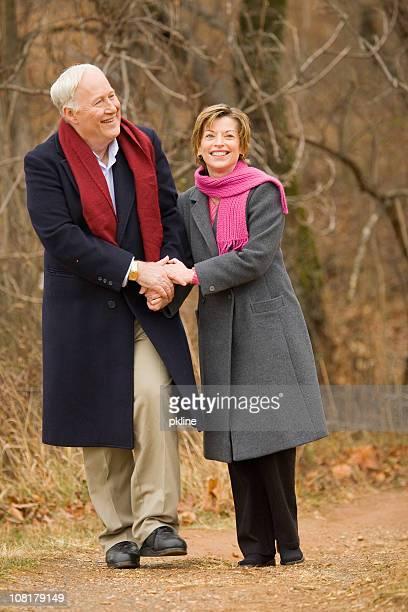年配のカップルと手をつなぐ歩く