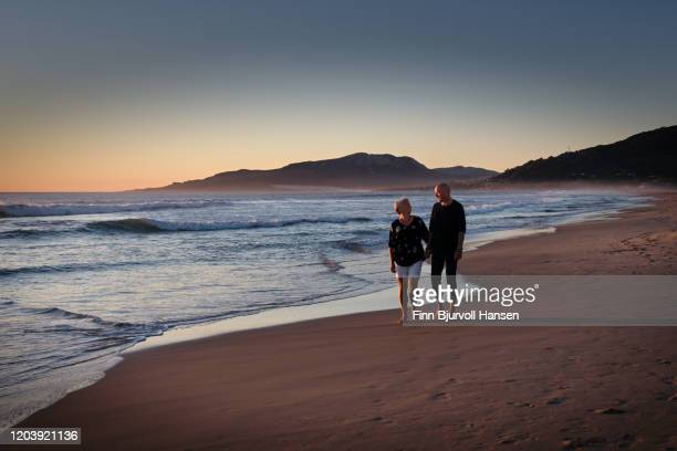 senior couple walking at the beach looking at eachother - finn bjurvoll stock pictures, royalty-free photos & images