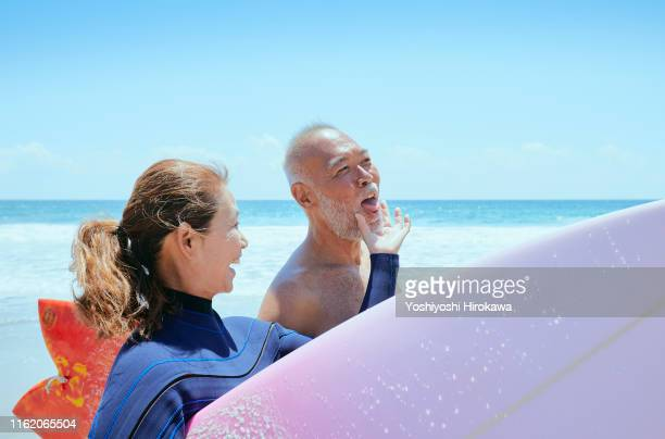 senior couple walking beach - protruding stock pictures, royalty-free photos & images