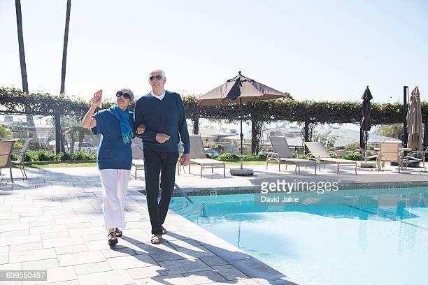 Senior couple walking beside swimming pool
