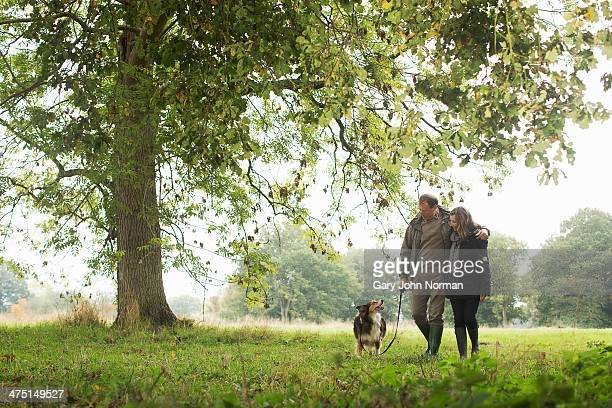 Senior couple walking dog, Norfolk, UK