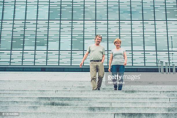 Senior couple walking down stairs of business building