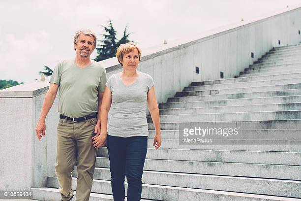 Senior couple walking hand in hand by the stairs