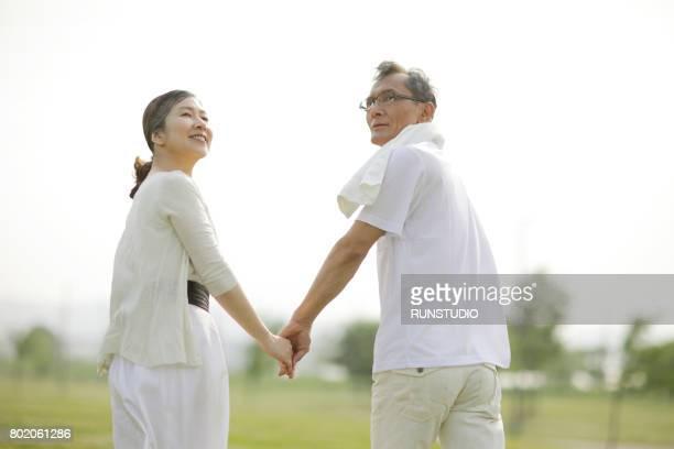 senior couple walking hand in hand in the park - 気が若い ストックフォトと画像