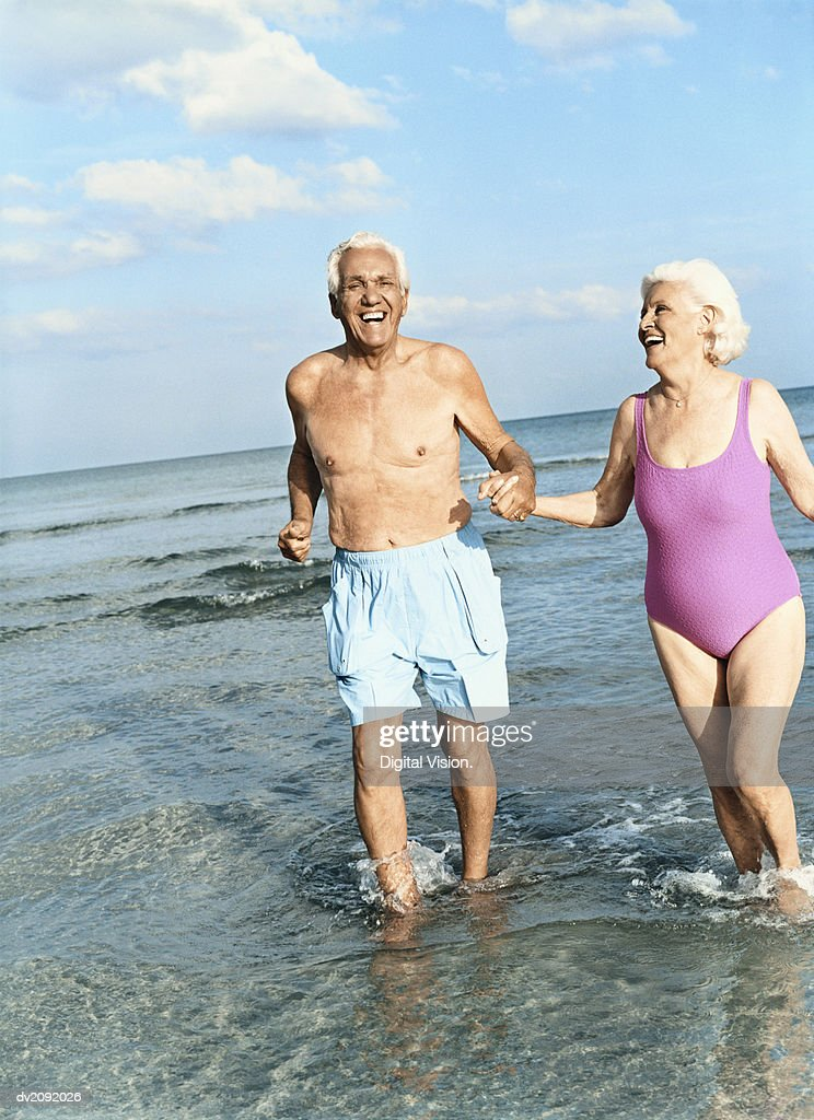 Senior Couple Walking Hand in Hand in the Surf : Stock Photo