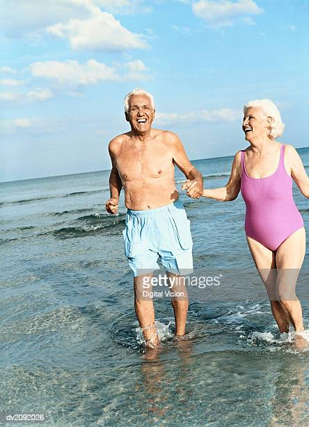Senior Couple Walking Hand in Hand in the Surf