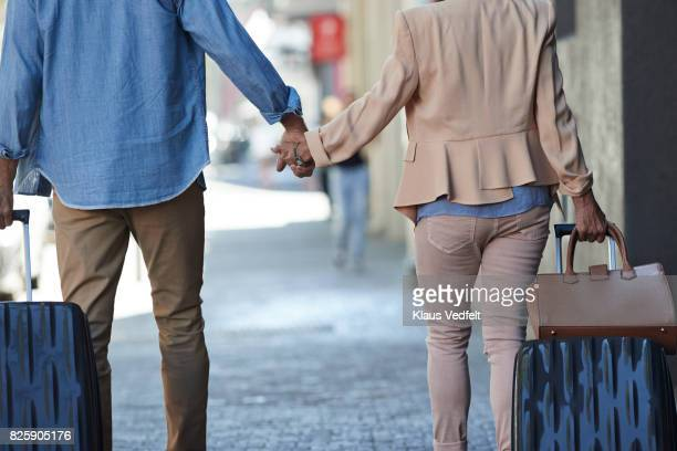 Senior couple walking hand in hand with rolling suitcases on city street
