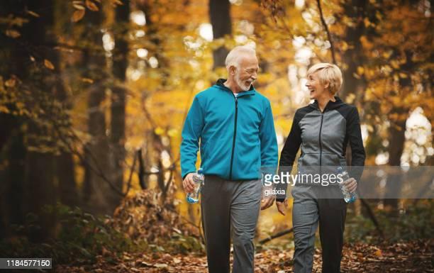 pareja mayor caminando en un bosque. - andar fotografías e imágenes de stock