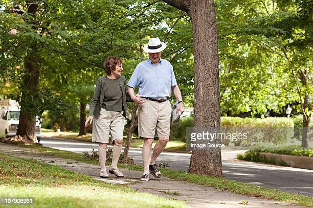 senior couple walking in neighborhood - continente americano foto e immagini stock