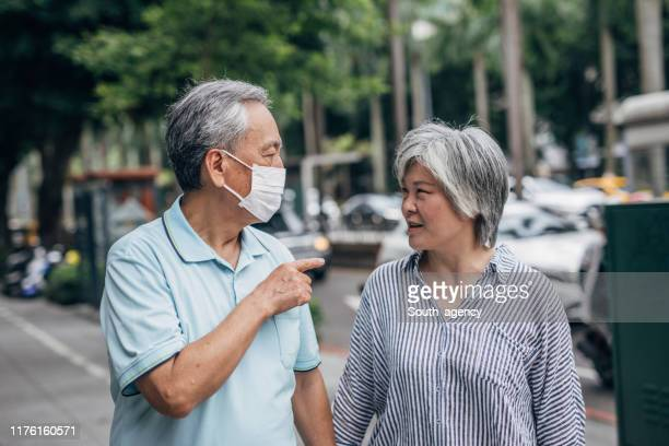 senior couple walking in park - surgical mask stock pictures, royalty-free photos & images