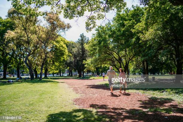 senior couple walking in public park - public park stock pictures, royalty-free photos & images