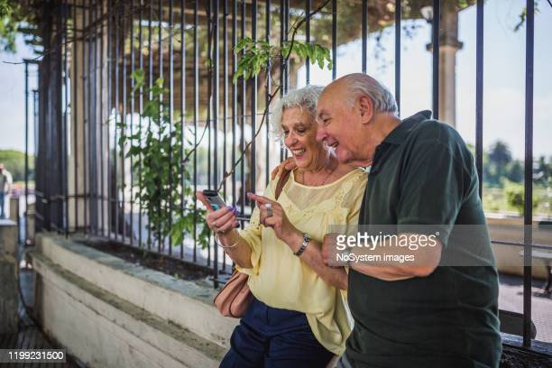 senior couple walking in the park, using a mobile phone - buenos aires stock pictures, royalty-free photos & images