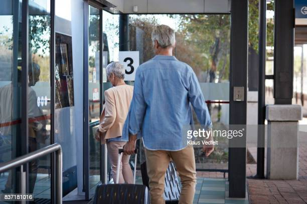 Senior couple walking into bus, from public transport platform
