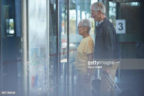 Senior couple walking into bus, from public transport platform