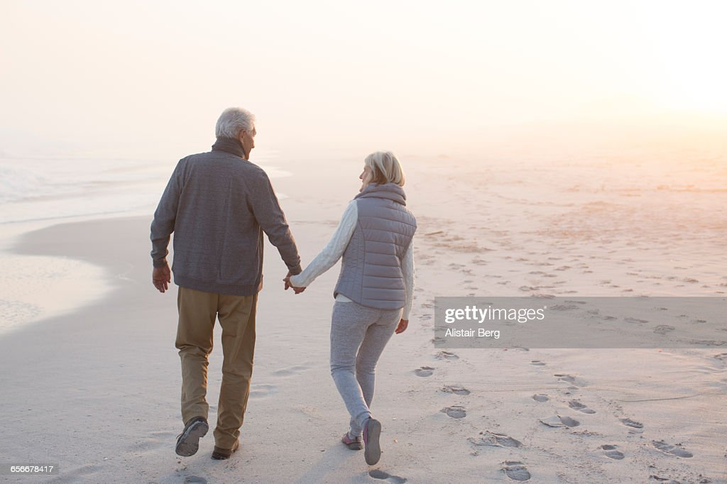 Senior couple walking on a beach together : Foto de stock