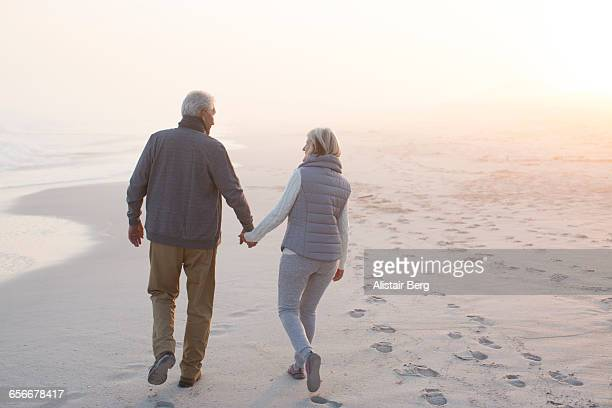 senior couple walking on a beach together - heterosexual couple photos - fotografias e filmes do acervo