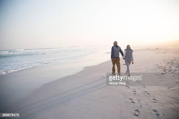 senior couple walking on a beach together - spoor vorm stockfoto's en -beelden