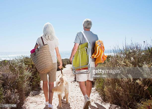senior couple walking on beach path with dog - woman carrying tote bag stock photos and pictures