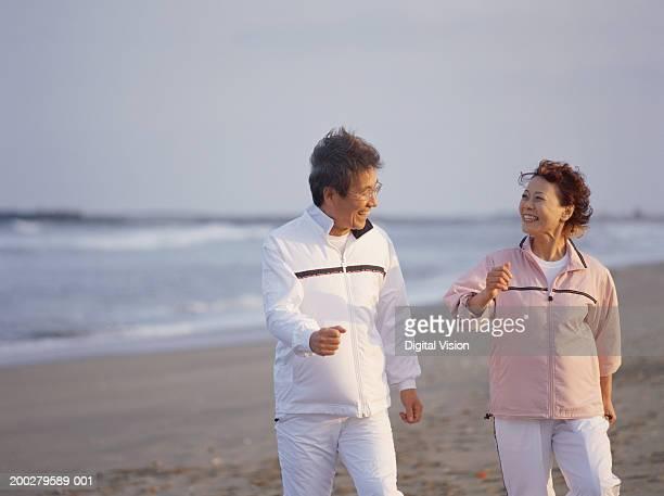 Senior couple walking on beach, smiling