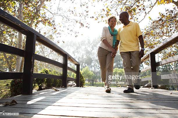 Senior couple walking on footbridge in park