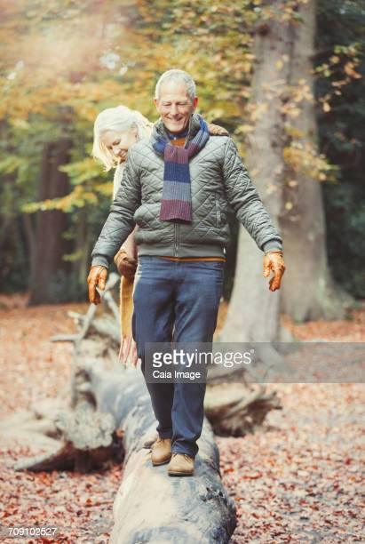 Senior couple walking on log in autumn woods