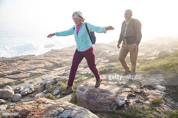 senior couple walking outdoors together - actieve ouderen stockfoto's en -beelden