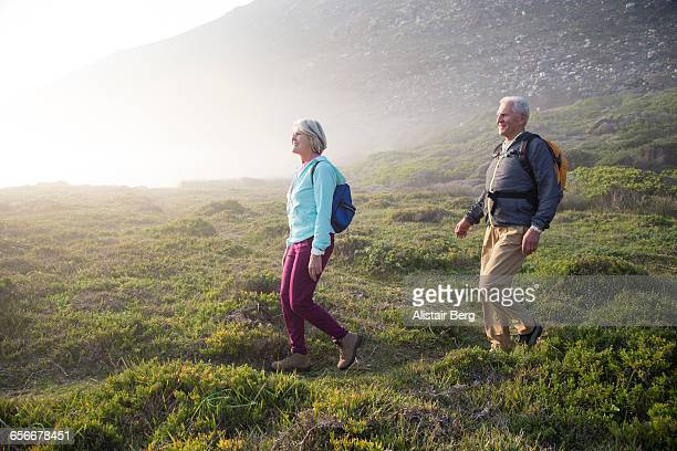 senior couple walking outdoors together - marcher photos et images de collection