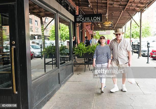 senior couple walking sidewalk of downtown old market omaha nebraska - nebraska stock photos and pictures