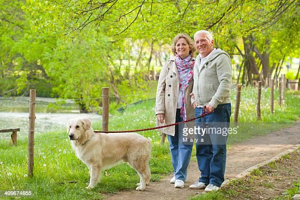 Senior couple walking their dog.