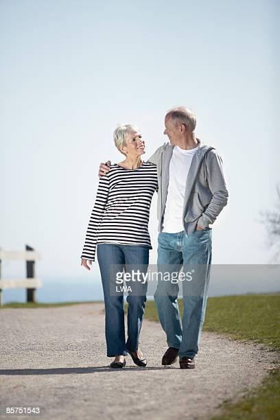 senior couple walking through park - só adultos imagens e fotografias de stock