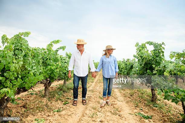 Senior couple walking through vineyards.