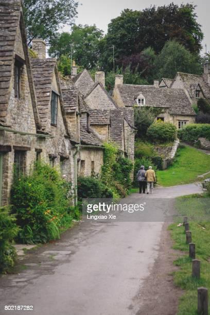 senior couple walking together at cotswolds village of bibury, england - steen bouwmateriaal stockfoto's en -beelden