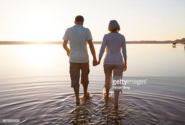senior couple walking together on a beach - plus fours stock photos and pictures