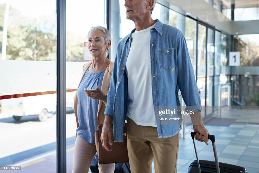 Senior couple walking together on public transport station : Stock Photo