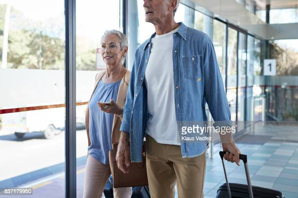 Senior couple walking together on public transport station
