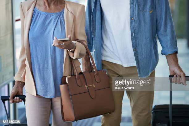 senior couple walking together on public transport station - luggage stock photos and pictures