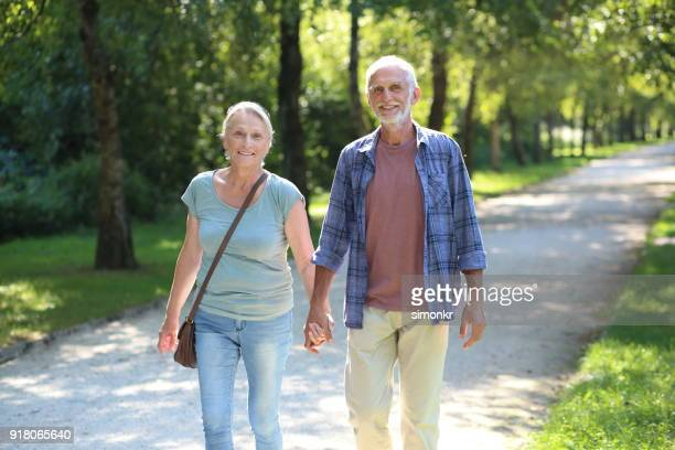 senior couple walking together - blue purse stock pictures, royalty-free photos & images