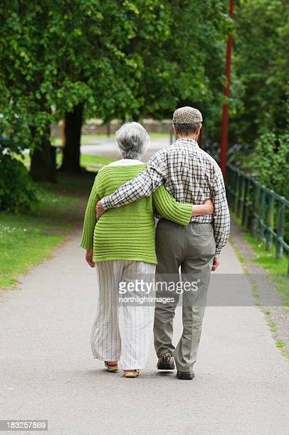 A senior couple walking together while holding each other