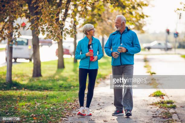 senior couple walking together with water bottles - walker stock photos and pictures