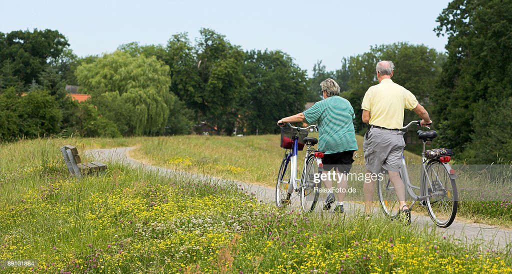 Senior couple walking with bicycles in summer on dyke : Stock Photo