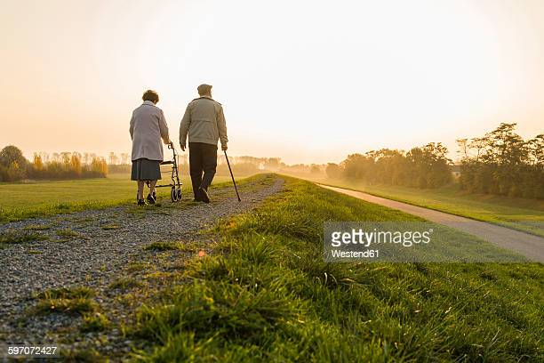 Senior couple walking with walking stick and wheeled walker in the nature