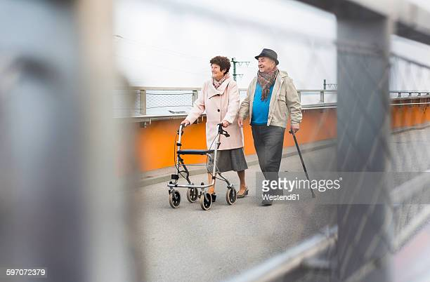 Senior couple walking with walking stick and wheeled walker