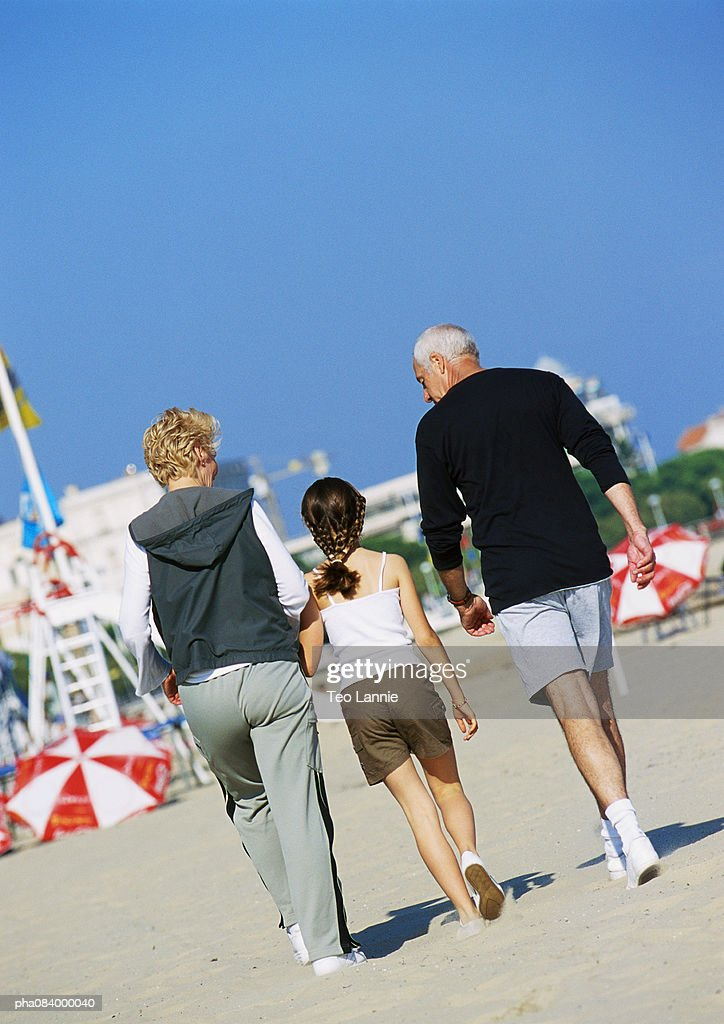 Senior couple walking with young girl on the beach, rear view. : Stockfoto