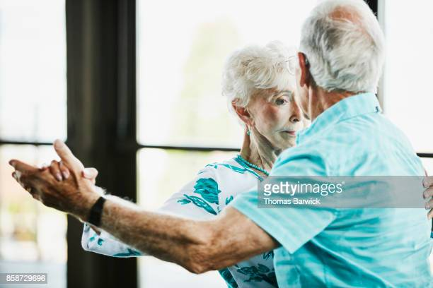 Senior couple waltzing during dance in community center
