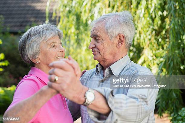 Senior couple waltzing in garden