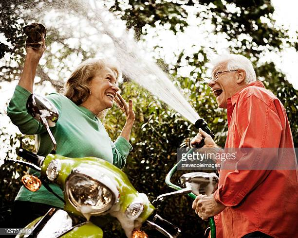 Senior Couple Washing Green Scooter